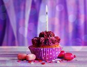 foto of sugarpaste  - Tasty cupcake on bright purple background - JPG