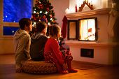 stock photo of little kids  - Father and his two little kids sitting by a fireplace in their family home on Christmas eve - JPG