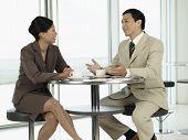 Постер, плакат: Бизнесмены сидя за столом разговаривали друг с другом