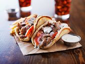 stock photo of gyro  - greek gyros with tzatzikii sauce and fries - JPG
