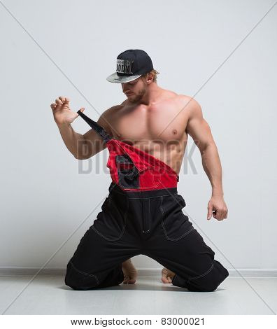 muscular construction worker in overalls. kneeling