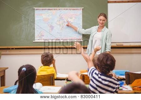 Teacher giving a geography lesson in classroom at the elementary school