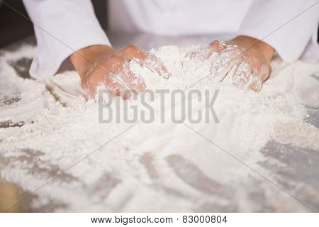 Close up of baker kneading dough on counter in the kitchen of the bakery