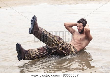 Handsome Soldier Doing Curl Ups At The Sea Water