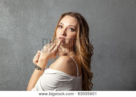 Attractive Young Woman With Finger On Lips