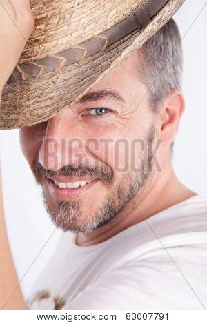 Smiling Cacasian Man With A Beard Lifting A Hat