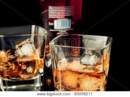 Whiskey With Ice In Glass On Black Background Near Bottle