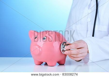 Doctor with pink piggy bank on blue background, close up