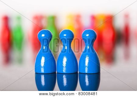 Three Colored Ludo Figures In Front Of Many Others
