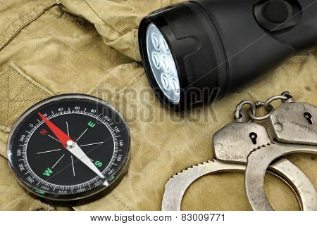 Black Searchlight, Compass And  Handcuffs On Weathered Handbag