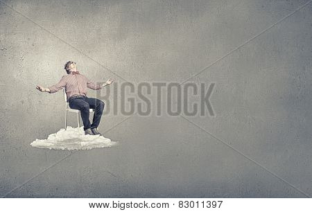 Troubled young man sitting in chair on cloud