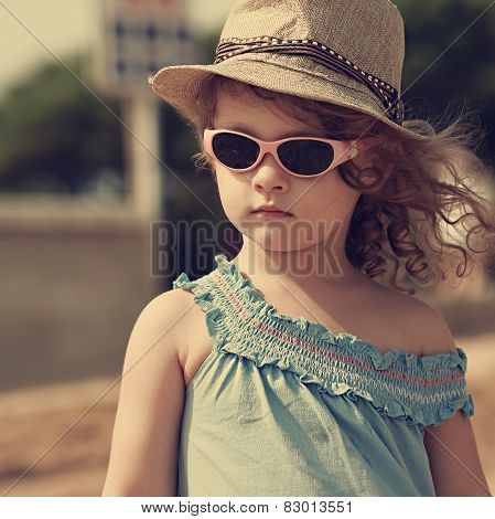 Kid In Sun Glasses And Fashion Hat Outdoors. Vintage Closeup Portrait