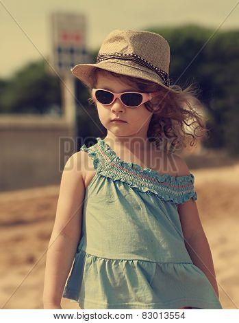 Beautiful Moden Kid Girl In Hat And Sun Glasses Looking Outdoors