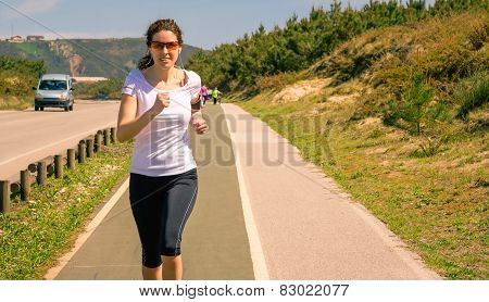 Young woman with earphones listening music and running