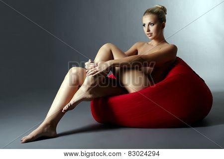 Beautiful naked woman sitting on red pouf