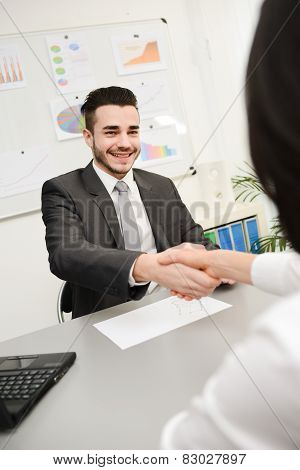handsome young businessman in transaction shaking hand with client
