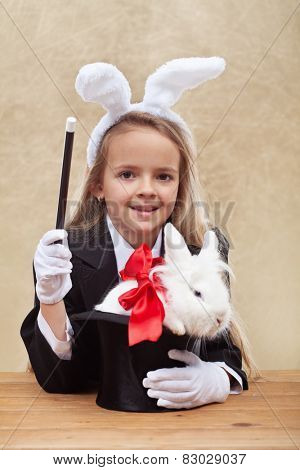 Happy magician girl wearing bunny ears holding white rabbit in a hat- shallow depth of field
