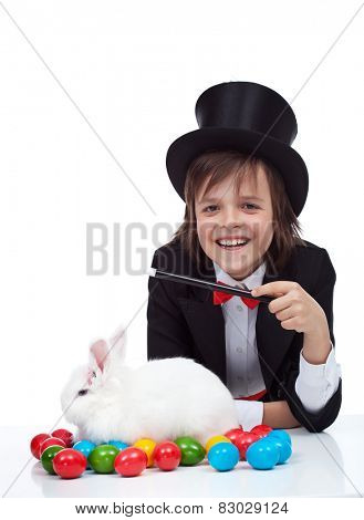 The magic of easter - happy magician boy conjuring a grumpy rabbit and colorful eggs, isolated