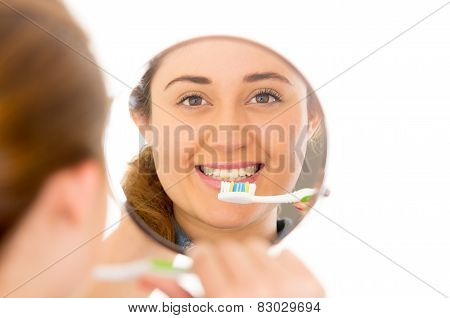beautiful young smiling woman brushing teeth