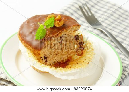 close up of chocolate muffin on white plate and checkered dishtowel
