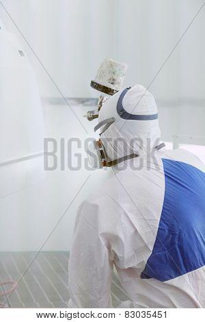 Automobile repairman painter paints the details for body repair