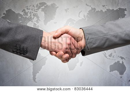 Businessmen shaking hands in front of a world map