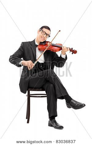 Vertical shot of a young violinist playing a violin seated on a chair isolated on white background