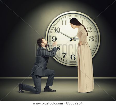 angry young woman staring at latecomer crying man on one knee. concept photo in dark empty room with big white clock on the wall