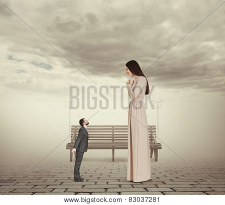young beautiful woman looking at small kissing man and smiling. concept photo in foggy park