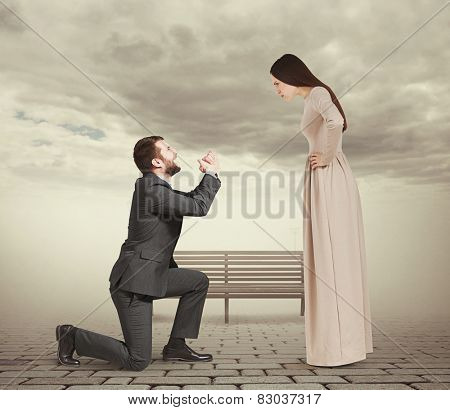 beautiful woman looking at man standing on knee and apologizing. photo in foggy park