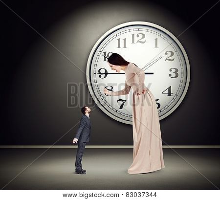 angry yelling woman showing fist and looking at small kissing man. concept photo in empty dark room with big white clock on the wall