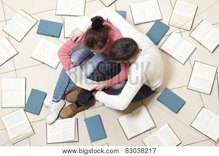 Young couple lying on floor with books and reading, top view. Blurred text is unreadable