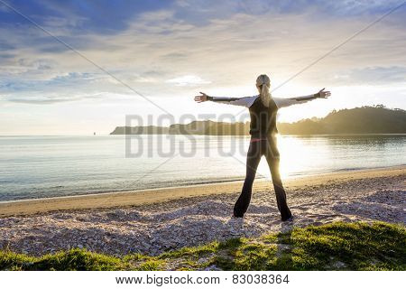 Healthy happy woman enjoying a sunny morning on the beach