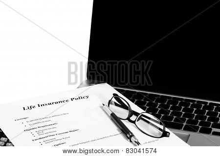 Life Insurance With Laptop And Reading Glasses