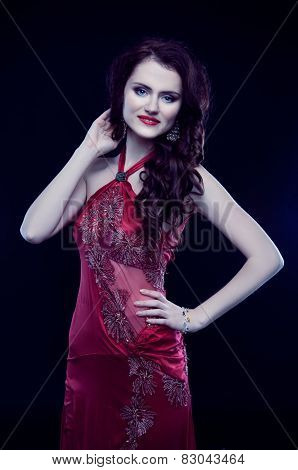 Beautiful Redheaded Woman With Long Curly Hair In Red Evening Dress