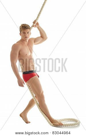 Handsome male model posing in underwear with rope
