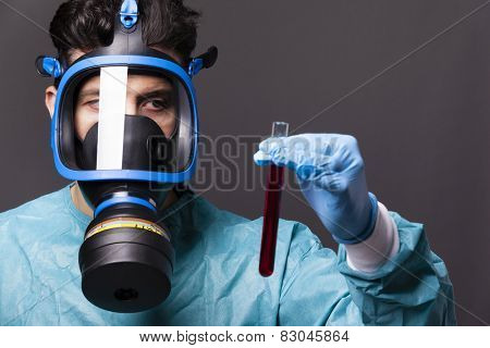 Scientist holding a sample of blood on grey background