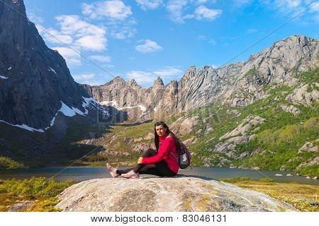Young Tourist Woman Is Sitting  On Stone Near Mountain Lake