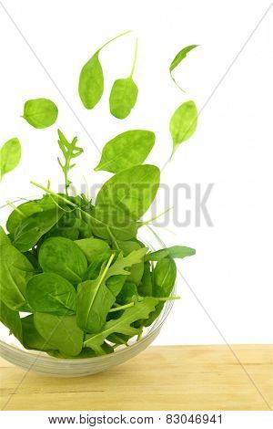 Fresh green salad with some leaves flying out of a bowl isolated