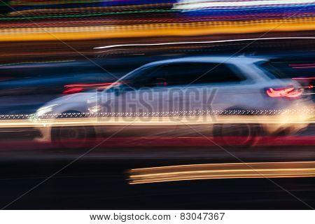 White Compact Car In A Blurred City Scene