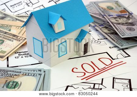 Model  house and construction plan with the word sold