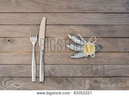 Three sardines and fork with knife