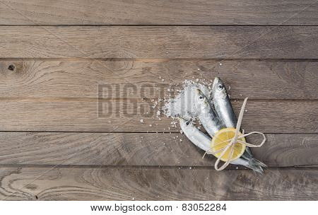 Three sardines wrapped with lemon on wooden table