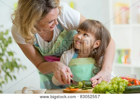 mother and daughter cooking and cutting vegetables on kitchen