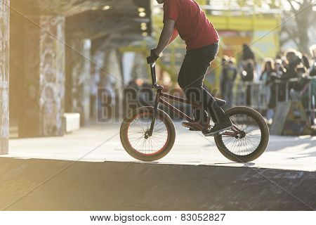 Anonymous bmx biker in a skate park with a blurred crowd watching in the sunlight