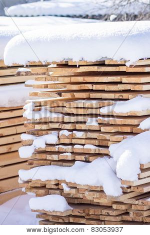 Stack Of Sawn Planks Covered With Snow