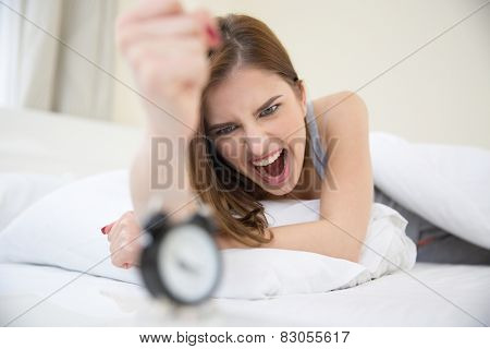 Angry woman who woke up very early to call an alarm clock in the bedroom