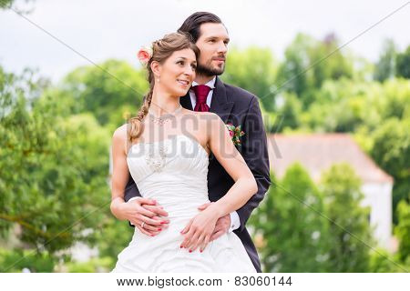 Wedding bride and groom outside in the garden, groom embracing bride