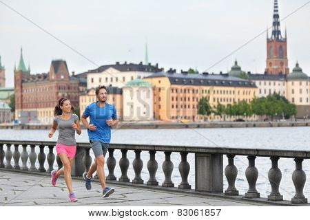 Fit fitness exercise people, healthy runners running in Stockholm city cityscape skyline. Riddarholmskyrkan church in the background, Sweden, Europe. Healthy multiracial young adults.