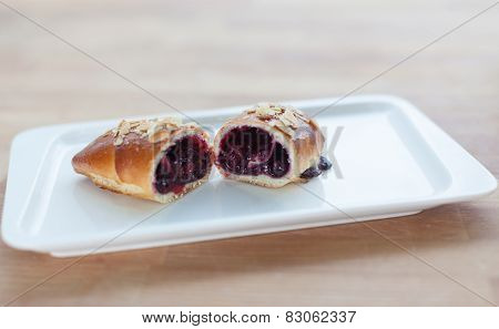 Beautiful delicious cake with berry jam filling on a plate. Cut in half.